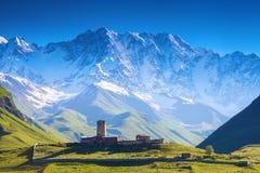 Eine faszinierende Ansicht über Ushguli-Dorf am Fuß von Schnee-mit einer Kappe bedeckt Lizenzfreie Stockfotos