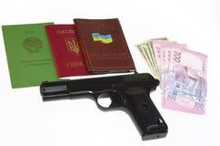 Eine Faustfeuerwaffe, ein Pass und ein Geld stellten auf eine weiße Hintergrundbasis ein Stockbild