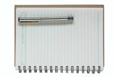Eine Feder auf einem gewundenen Notizbuch Lizenzfreies Stockfoto