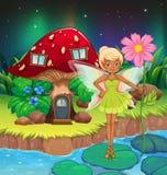Eine Fee, die eine Blume nahe dem roten Pilzhaus hält Stockbild