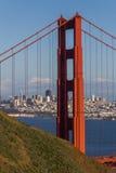 Eine vertikale Ernte des Nordturms Golden gate bridges mit der Nachmittagssonne, die auf San Francisco im Hintergrund scheint Lizenzfreies Stockbild