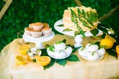 Eine festliche kandi Stange verziert in einer tropischen Art mit Zitronenkuchenmuffins und Eibische und helle Ballone stockfotografie