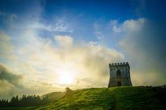 Eine Festung auf einem grünen Hügel während eines schönen Sonnenuntergangs stockbilder