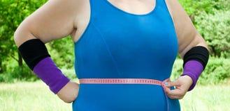 Eine fette Frau in einer blauen Klage auf dem grünen Gras, zum des Volumens des Bauches zu messen Stockfoto