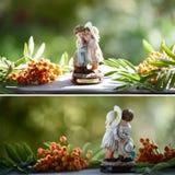 Eine Figürchen eines Jungen und des Mädchens auf einem natürlichen grünen Hintergrund, Ebereschenbeeren Lizenzfreies Stockbild