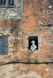 Eine Figürchen im Fenster eines alten Hauses lizenzfreies stockfoto