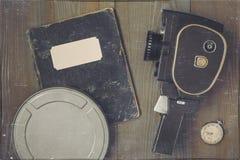 Eine Filmkamera, eine Uhr, ein Kasten des Filmes und ein altes Notizbuch Stockfotografie