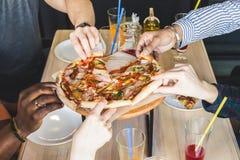 Eine Firma von den multikulturellen jungen Leuten in einem Caf? Pizza, trinkende Cocktails essend, Spa? habend stockfotografie