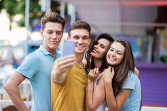 Eine Firma von schönen Freunden ist, machend lachend und selfie im netten Sommercafé Unterhaltung, gute Zeit habend lizenzfreies stockfoto