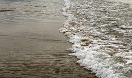 Eine flache Welle auf sandigem Strand Stockfotografie