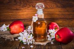 Eine Flasche Apfelweinessig (Apfelwein), frische Äpfel und Applebaumblumen auf einem hölzernen Hintergrund Stockfotografie
