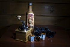 Eine Flasche bedeckt durch Birkenrinde, Kaffeemühle und Metall des Gold drei Lizenzfreie Stockbilder