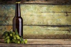 Eine Flasche Bier mit Bündel Hopfen auf hölzernem Hintergrund Stockfotografie
