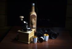 Eine Flasche, Kaffeemühle, Ferngläser und drei Goldmetallgläser Stockfoto