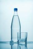 Eine Flasche kaltes Wasser, Eis und leeres Glas Lizenzfreies Stockbild