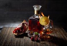 Eine Flasche Kognak, Whisky mit einem Brennglas und Früchte auf hölzernem Hintergrund Lizenzfreies Stockfoto