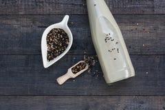 Eine Flasche Milch des indischen Sesams auf schwarzem hölzernem bBackground Stockbild