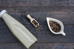 Eine Flasche Milch des indischen Sesams auf schwarzem hölzernem Hintergrund Stockfotografie