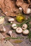Eine Flasche Olivenöl umgeben durch Pilze, Rosmarin und Knoblauch Gemüse eingestellt auf einen Hintergrund des braunen Papiers Stockfoto