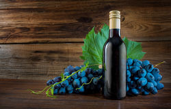 Eine Flasche Rotwein mit einer Rebtraube lizenzfreie stockbilder