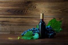 Eine Flasche Rotwein mit Trauben lizenzfreies stockfoto