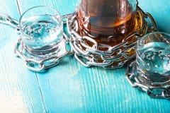 Eine Flasche Rum und zwei Gläser folgendes eingewickelt mit einer Metallkette Lizenzfreie Stockbilder