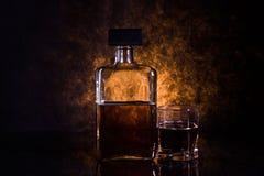 Eine Flasche und ein Glas des alkoholischen Getränks, Beifall Stockbild