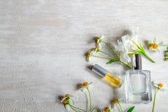 Eine Flasche weißes Parfüm und Blumen mit Blättern lizenzfreies stockfoto