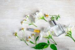 Eine Flasche weißes Parfüm und Blumen mit Blättern lizenzfreie stockfotos