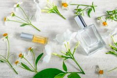 Eine Flasche weißes Parfüm und Blumen mit Blättern lizenzfreie stockfotografie