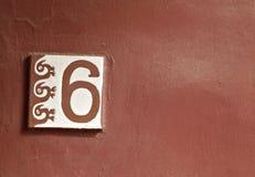 Eine Fliese der Nr. 6 mit Mayasymbol auf rotem Hintergrund Stockbilder