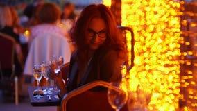 Eine flirty Frau, die durch Tabelle im Freienrestaurant - Halten eines Glases Champagners sitzt stock video