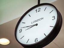 Eine Flughafenuhr, die London-Zeitzone zeigt Stockbild