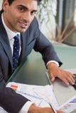 Eine fokussierte Verkaufsperson, die Statistiken studiert Lizenzfreie Stockfotos