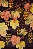 Eine Fotografie von geschmiedeten Trauben, gemalt in den warmen orange Tönen auf einem hölzernen Hintergrund Hintergrund auf dem  Stockbilder
