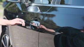 Eine Frau öffnet die Tür zu ihrem neuen schwarzen Auto kaufte das Auto an der Verkaufsstelle stock video