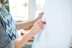 Eine Frau übergibt Farben auf einem weißen hölzernen Segeltuch in einem Funktionsraum Fenster auf einem Hintergrund Weiße Schablo Lizenzfreies Stockfoto