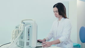 Eine Frau arbeitet mit einem Ultraschallgerät in der Klinik stock video