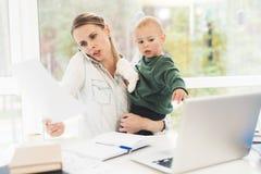 Eine Frau arbeitet während des Mutterschaftsurlaubs zu Hause Eine Frau arbeitet und interessiert sich für ein Kind gleichzeitig lizenzfreies stockbild