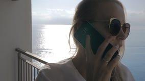 Eine Frau auf einem Balkon sprechend mit einem Telefon und einer Seeansicht hinter sie stock footage