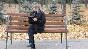 Eine Frau auf einer Bank mit dem Tablet stock video