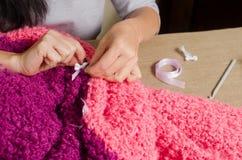 Eine Frau befestigt einen weißen Bogen zu einem gestrickten eigenhändig Flieder-rosa Winkel des Leistungshebels stockbilder