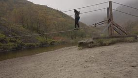 Eine Frau beginnt, eine Drahtbrücke über dem Nevis-Fluss, Schottland zu kreuzen stock video