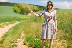Eine Frau beim Per Anhalter fahren weg von der Stra?e w?hrend des sonnigen Tages lizenzfreie stockfotos