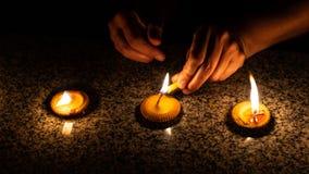Eine Frau beleuchtet drei thailändische angeredete Kerzen während Loy Krathong- oder Yeepeng-Festivals in Chiang Mai lizenzfreies stockfoto