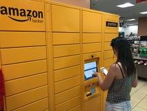 Eine Frau benutzt eine Amazonas-Schließfachstation stockbild