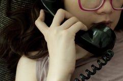 Eine Frau benutzt ein Weinlesetelefon Lizenzfreie Stockfotografie