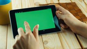 Eine Frau benutzt einen Tablet-PC an seinem Schreibtisch grüner Schirm ersetzen Stockfoto