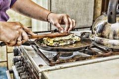 Eine Frau bereitet Frühstück zu Hause in der Küche zu Toast in einer Bratpfanne mit Eigrün und -speck Gesunde Nahrung Stockfotografie
