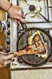 Eine Frau bereitet Frühstück zu Hause in der Küche zu Toast in einer Bratpfanne mit Eigrün und -speck Gesunde Nahrung Lizenzfreies Stockfoto
